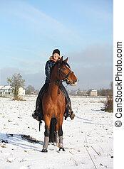 Teenager girl riding bay horse portrait