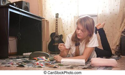 Teenager girl spending time at home drawing while lying on...