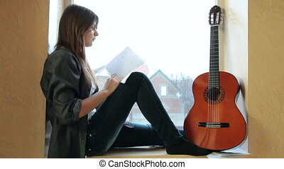 Teenager Girl Studying Guitar Chart At Home