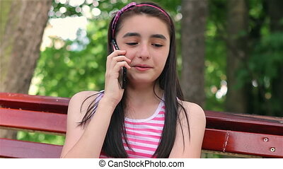 Teenager girl talking on smartphone in city park.