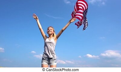 Teenager girl throws USA flag in the air - Teenager girl in...