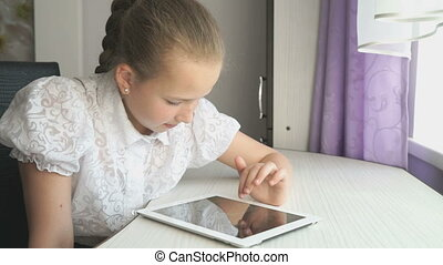 Teenager girl uses a digital tablet at the desk