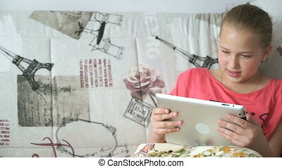 Teenager girl uses a digital tablet on the bed