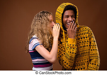 Teenager girl whispering to happy African man who is laughing