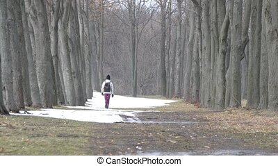 Teenager girl with backpack walks in winter in a park