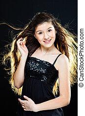 teenager girl with  beautiful long dark hair  on black