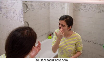 Teenager girl with blackheads, puts a black cosmetic mask on her face, looks in the mirror, facial skin care