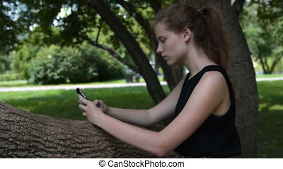 Teenager girl with cell in the park