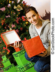Teenager girl with gift boxes, Christmas three behind her