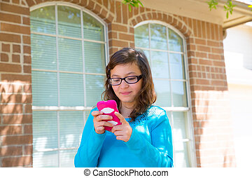 Teenager girl with glasses playing with smartphone