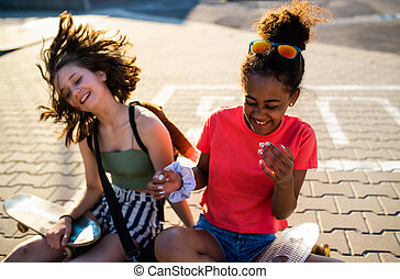 Teenager girls friends with skateboards sitting outdoors in city.