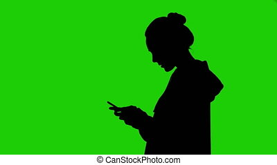 Teenager girl's silhouette with smartphone on green background