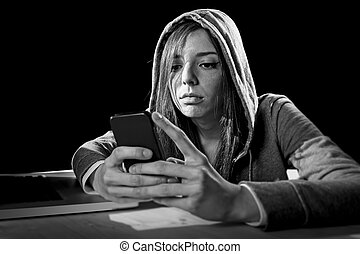teenager hacker girl in hood using mobile phone in internet cyber crime expert or cybercrime