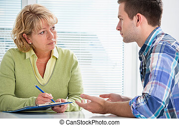 Teenager having a therapy session while therapist is taking ...