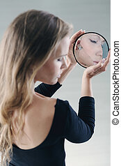 Teenager holding small broken mirror - Teenager with...