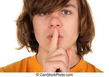 Teenager holds finger before lips