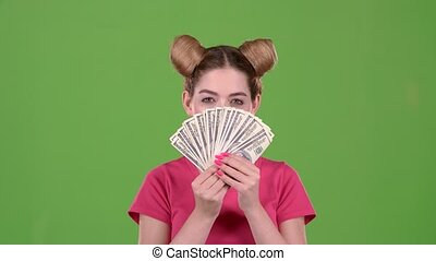 Teenager holds paper bills and winks. Green screen. Slow...