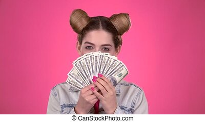 Teenager holds paper bills and winks. Pink background. Slow...