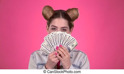 Teenager holds paper bills and winks. Pink background -...