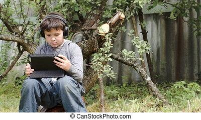 Teenager in earphones using touchpad outdoor