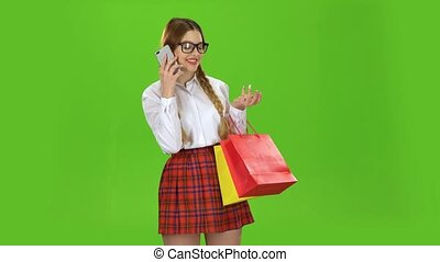 Teenager in glasses is talking on the phone and holding a packet of paper. Green screen