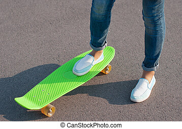 Teenager in jeans with a skateboard in the street.