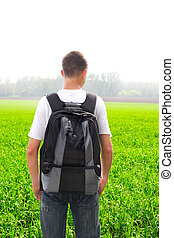 teenager in the field - teenager with knapsack in the summer...