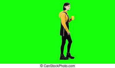 Teenager is drinking tea on the go. Green screen. Side view...