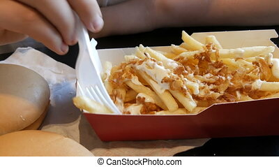 Teenager is eating fried french fries with onions and...
