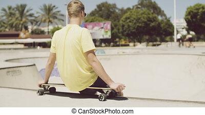 Teenager is Sitting on His Longboard