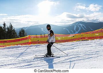 Teenager is skiing at a ski resort in the mountains