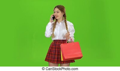 Teenager is talking on the phone and holding a packet of paper. Green screen