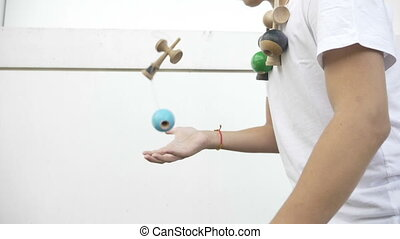 Teenager kendama collector juggling with toy outdoor ken...