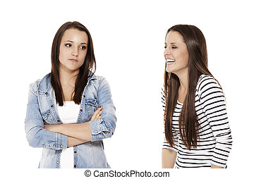 teenager laughing at her upset sister on white background