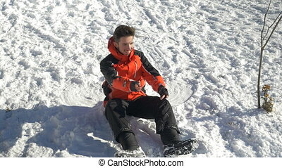 Teenager laying down in the snow making a snowball and eating snow
