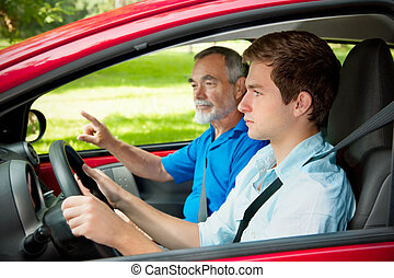 Teenager learning to drive with his driving instructor