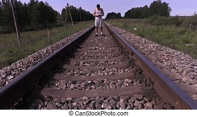 Teenager listen to music and walking by rail