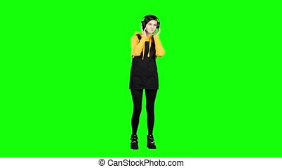 Teenager listens to music on headphones. Green screen