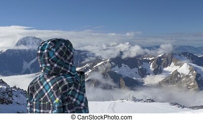 Teenager looking at the mountains, from a height of 4700 m. This is the main Caucasian ridge. Elbrus is the highest point in Europe. HD