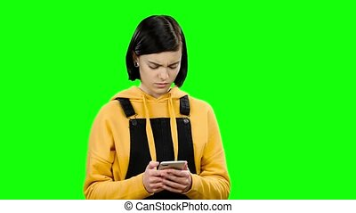 Teenager looks into the phone and sees strange photos. Green...