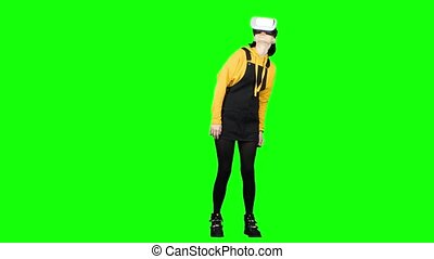 Teenager looks into virtual reality glasses. Green screen