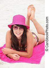 Teenager lying on the beach