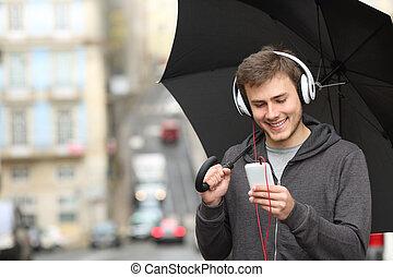 teenager, lytte musik til, hos, en, telefon, under, den, regn