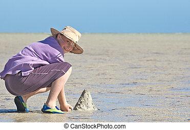 teenager making sandcastles on the beach