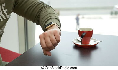 Teenager man checking for new email on smartwatch at a coffee shop