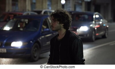 Teenager man waiting and checking smartphone in the night for Uber car order on urban street with car traffic