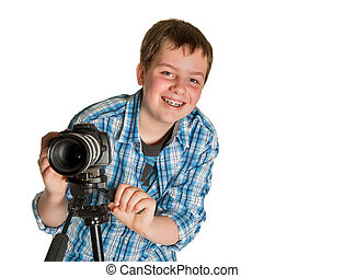 Young photographer teenager taking photos with a camera on a tripod