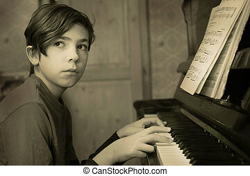 teenager pianist boy playing piano with music notes