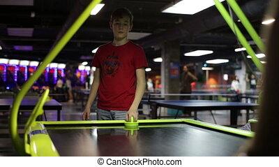 Teenager playing air hockey game