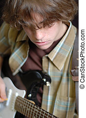 teenager playing guitar - fourteen year old teenage boy...